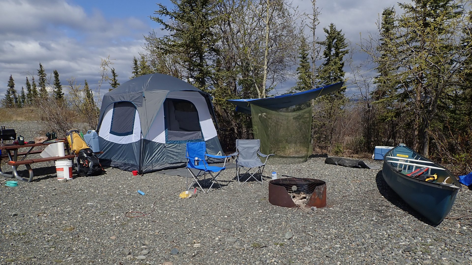 Camping site at Lake Louise with tent, fire, and canoe