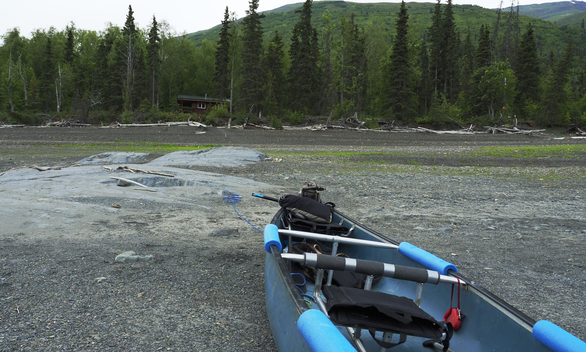 Canoe on rocky beach with cabin in the background