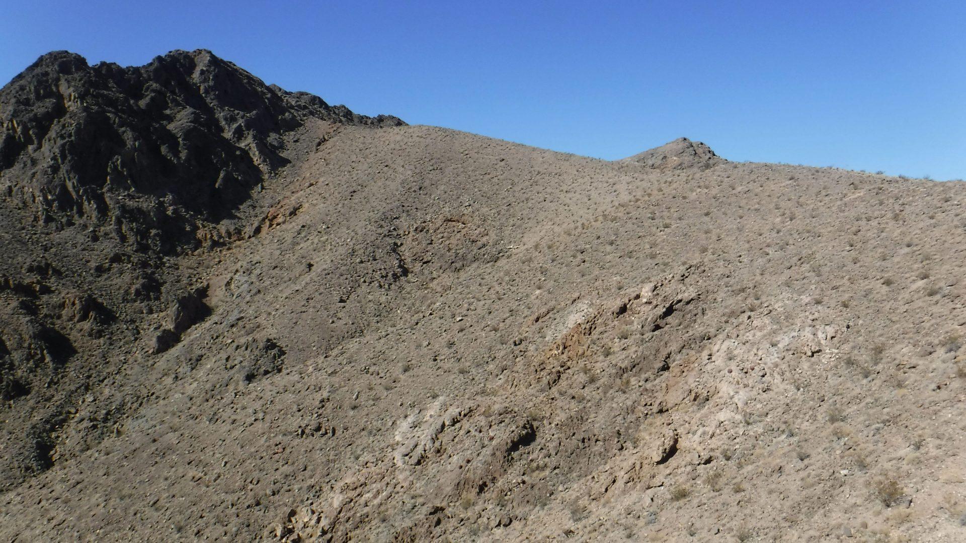 Desert ridgeline with a peak in the background
